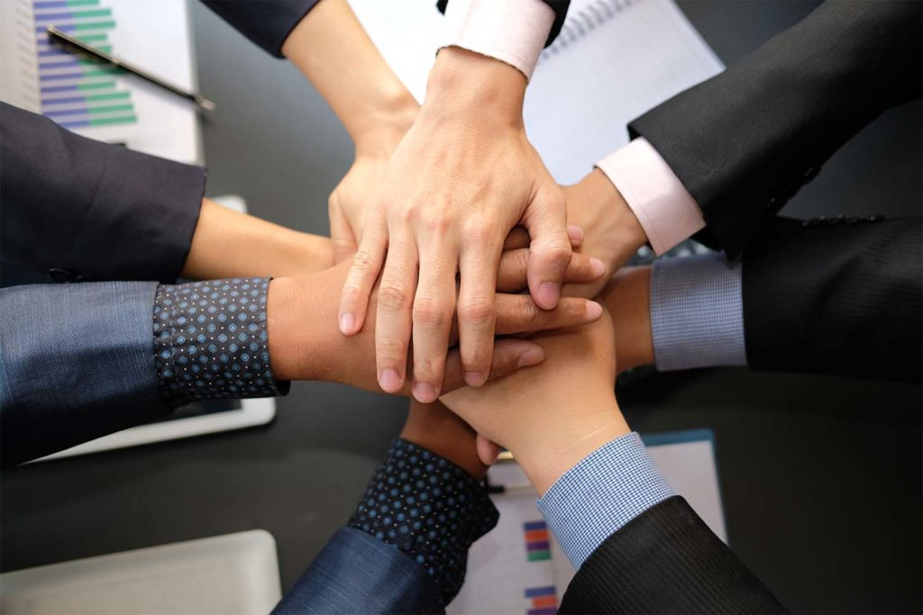businessman joining united hand, business team touching hands together after complete a deal in meeting. unity teamwork partnership corporate concept