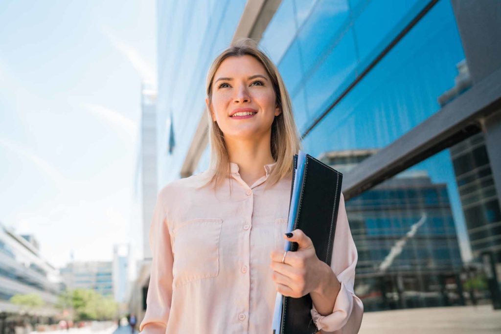 Portrait of young business woman standing outside office buildings. Business and success concept.