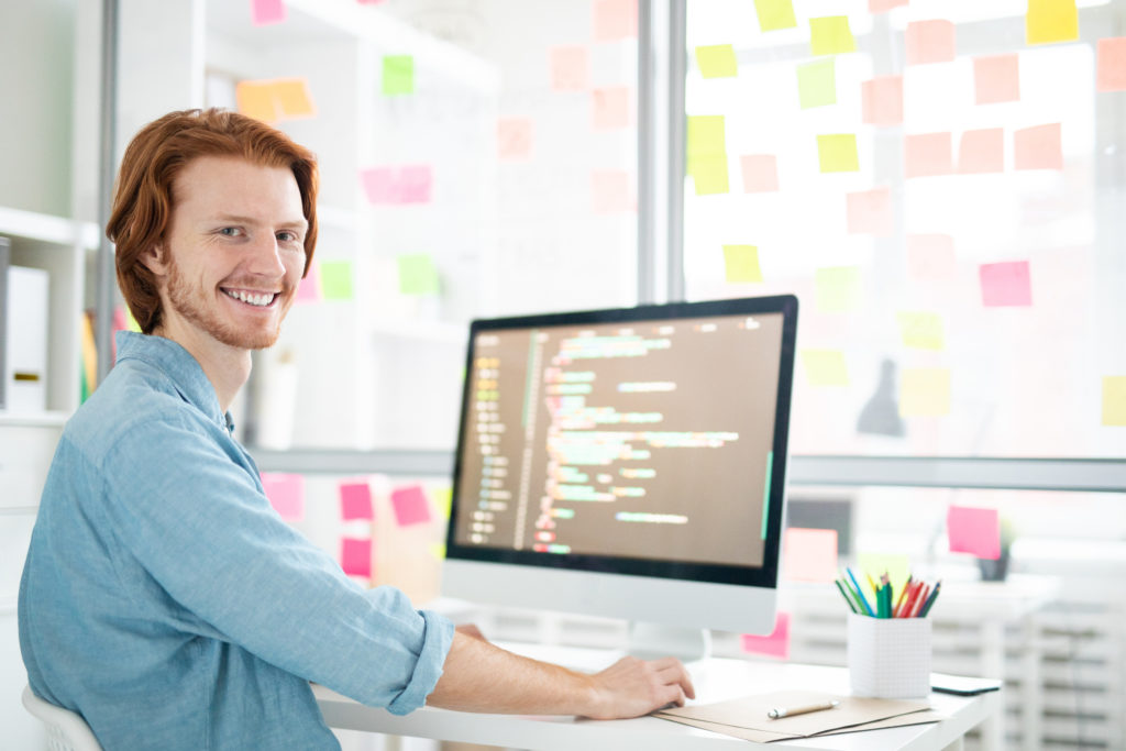 Young cheerful it-developer with toothy smile looking at you while sitting by workplace in front of computer screen