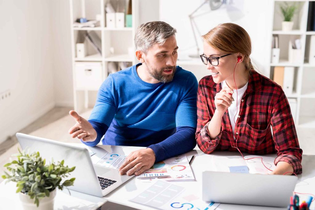 Cheerful optimistic young colleagues in casual clothing sitting at table and discussing marketing analysis in office: bearded man pointing at screen while explaining strategy to woman in earphones