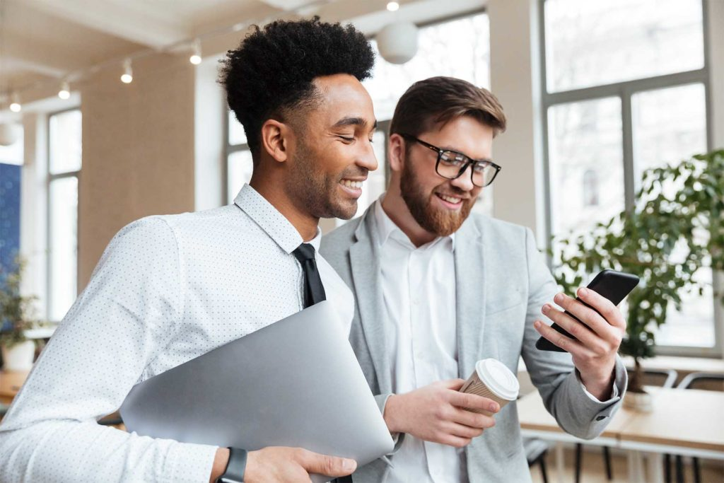 Image of happy businessmen colleagues talking with each other using mobile phone