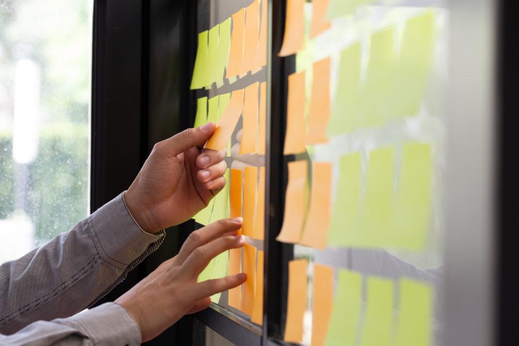 Pracownik IT dołącza karteczkę do tablicy zadań w biurze