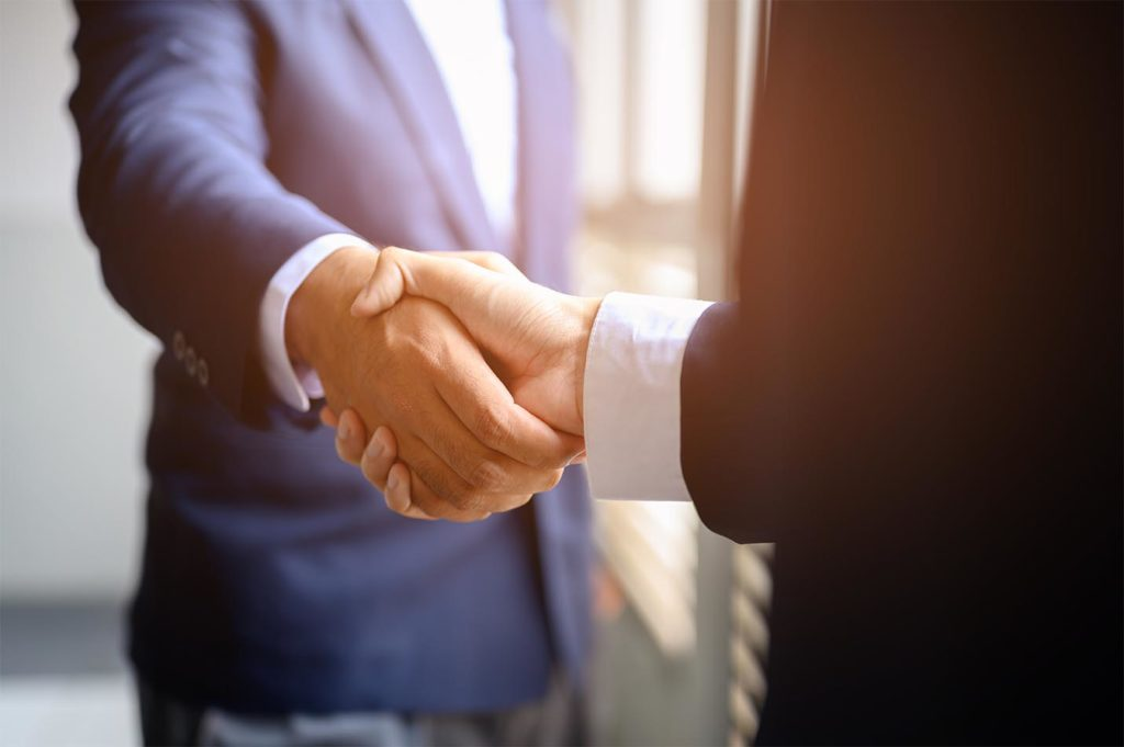 Two businessmen join hands for business cooperation