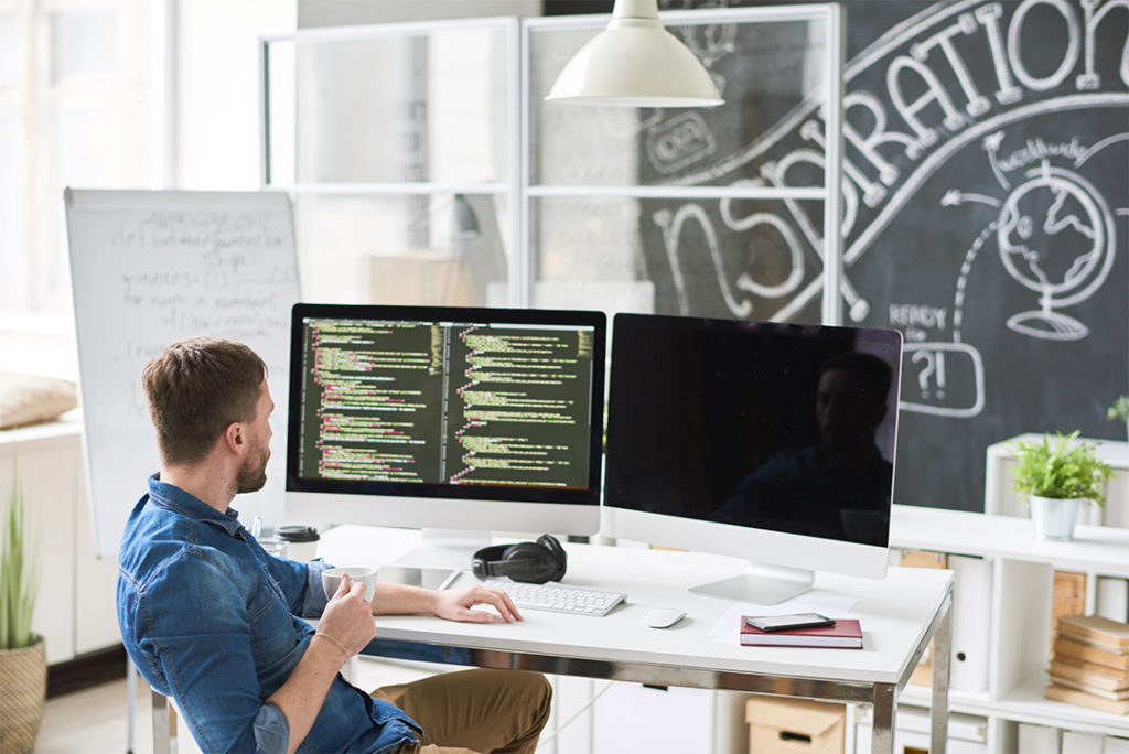 Male programmer analyzing code on two computer monitor