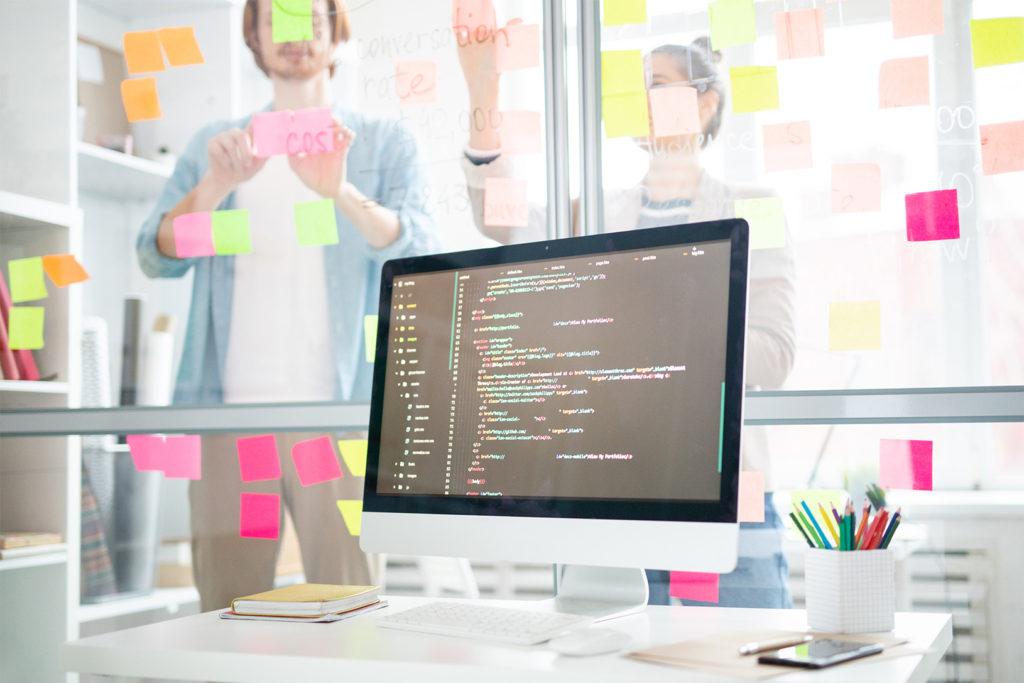Monitor na tle pracowników przyklejających kolorowe karteczki na przezroczystej tablicy