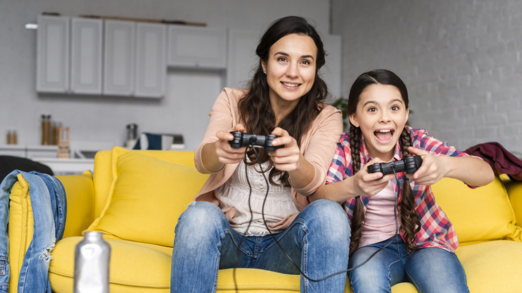 The woman and the girl are playing on the console