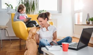 Woman sitting on the floor and Stroking dog at home while daughter sitting on the armchair and using tablet